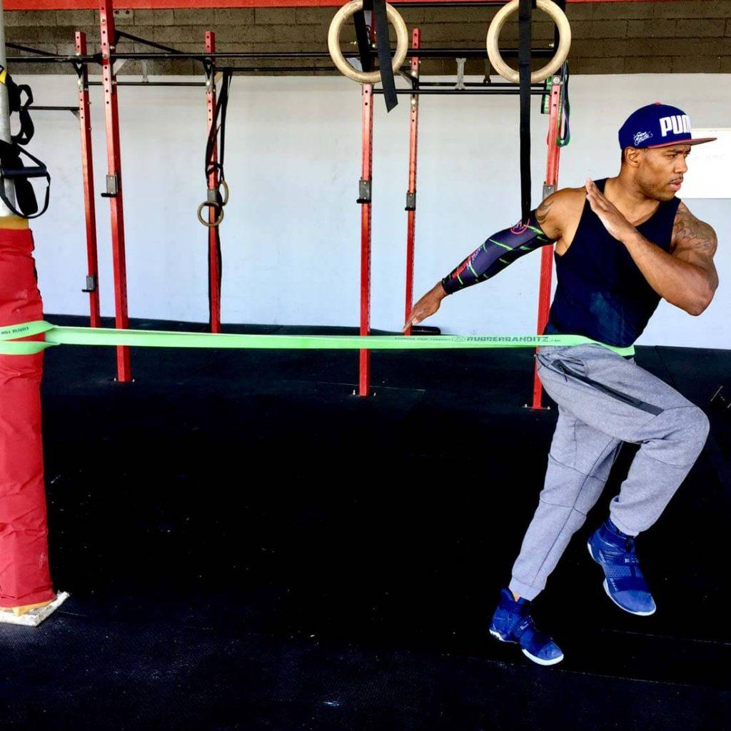Un atleta allena la corsa trattenuto da un elastico
