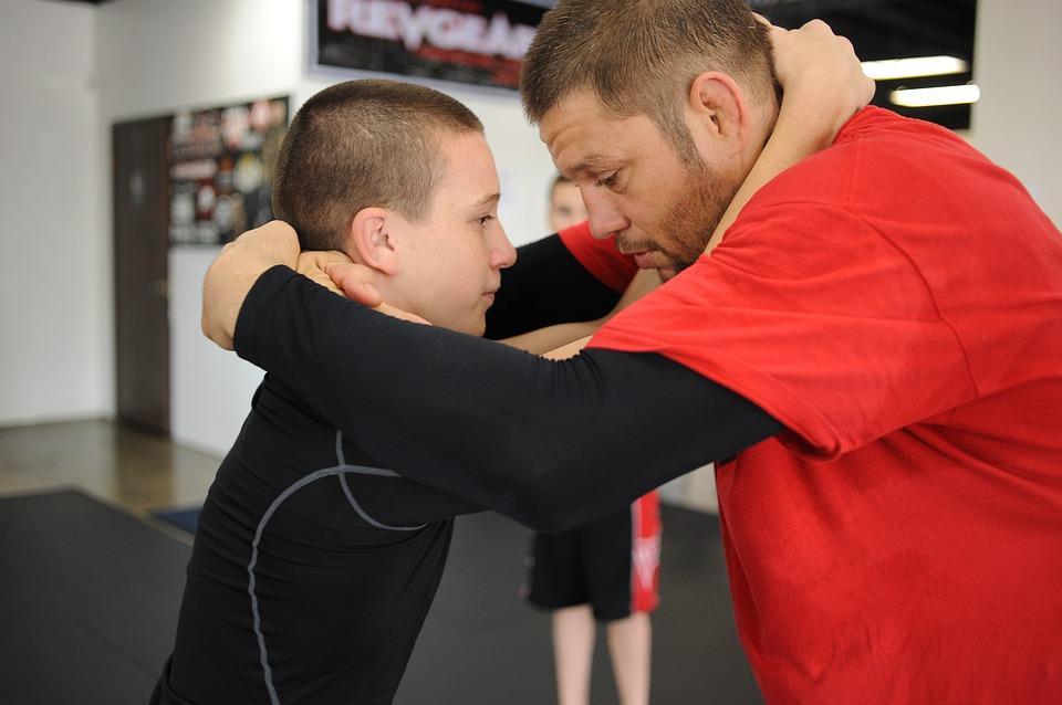 coach insegna le posizioni base della lotta in piedi ad un bambino