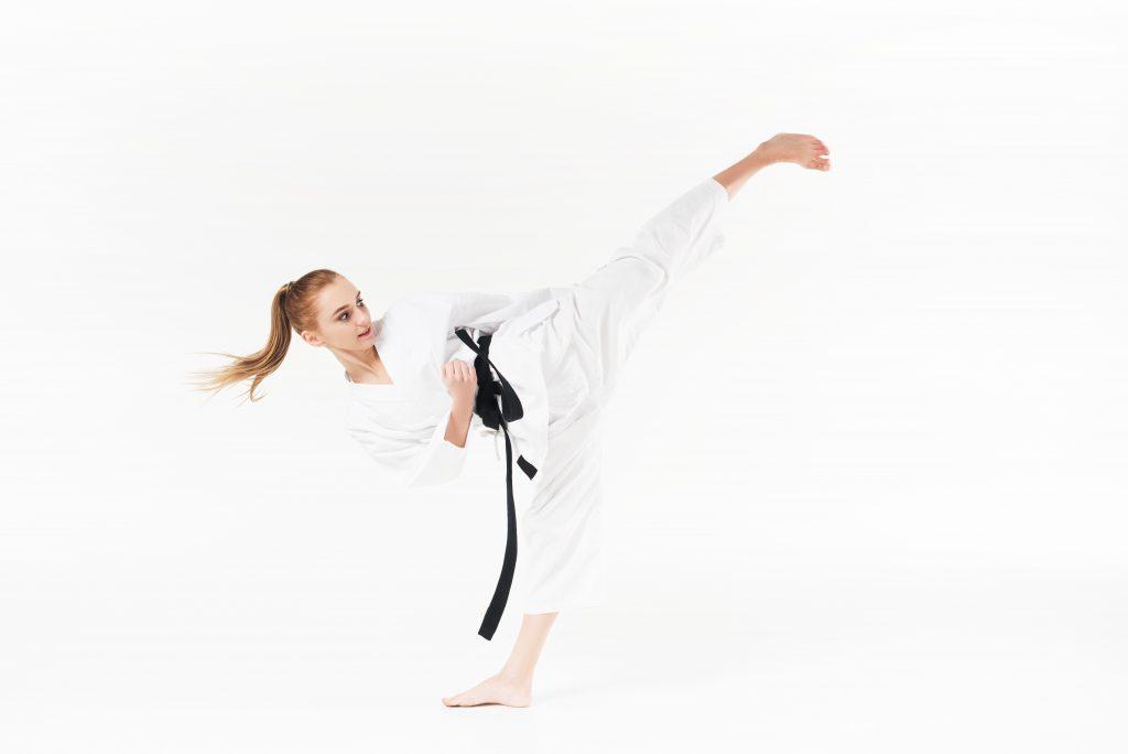 donna in karategi esegue un calcio laterale Yoko Geri